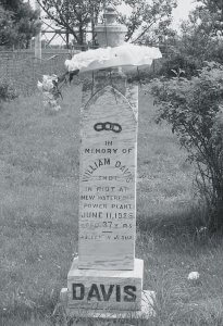 "A black and white photo of William Davis's tombstone. It is a white granite pillar reading, ""In memory of William Davis, shot in riot at New Waterford power plant, June 11, 1925, Aged 37 years, Asleep in Jesus."""