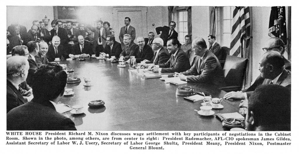 Caption reads: WHITE HOUSE President Richard M. Nixon discusses wage settlement with key participants of negotiations in the Cabinet Room. Shown in the photo, among others, are from center to right: President Rademacher, AFL-CIO spokesman James Gides, Assistant Secretary of Labor W.J. Usery, Secretary of Labor George Shultz, President Meany, President Nixon, Postmaster General Blount