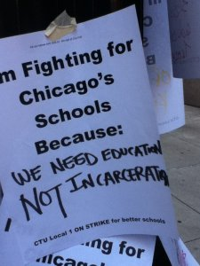 "Printed sign reads: ""I'm fighting for Chicago's Schools Because,"" with handwritten text below: ""We need education NOT incarceration."""